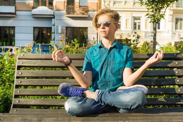 Подросток сидит в позе лотоса на скамейке в городском парке
