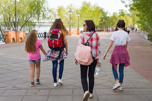 公園を歩いている子供と女性のグループ