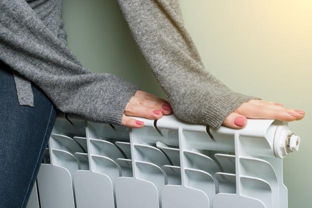 Женщина положила руки на радиатор