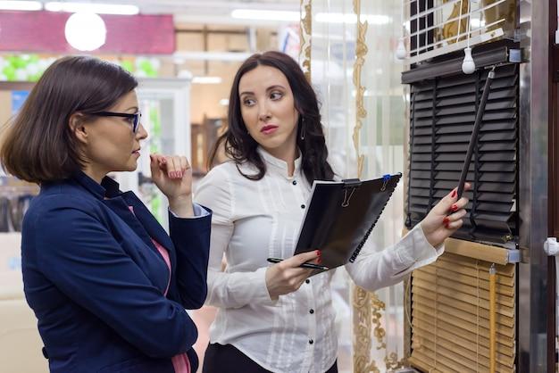 Женщина продавец показывает ткани для образцов жалюзи