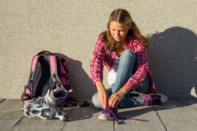 女の子はスニーカーと服のローラースケートを削除します
