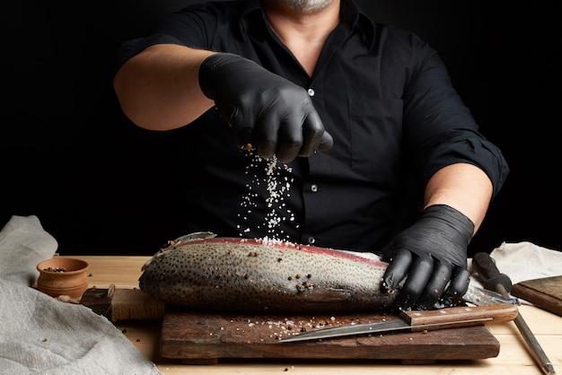 Шеф-повар в черной рубашке и черных латексных перчатках готовит филе лосося