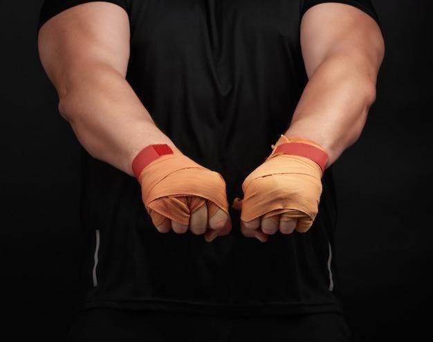 Взрослый мужчина в черной форме и мускулистом теле стоит в спортивной позе