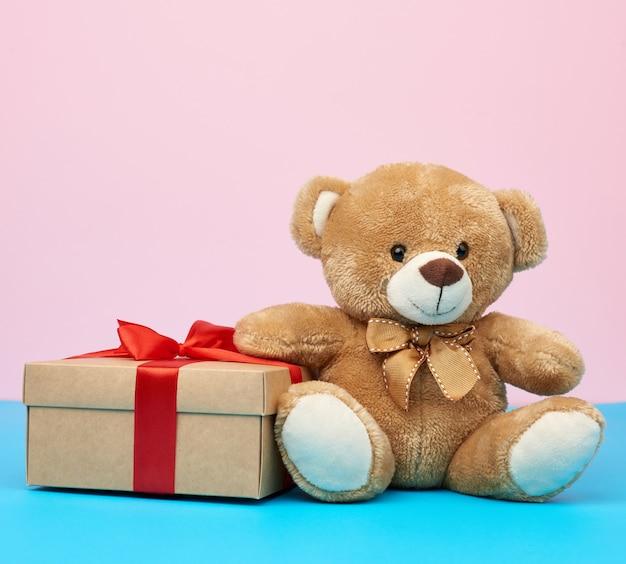 Милый маленький коричневый мишка держит коричневую коробку с красной лентой