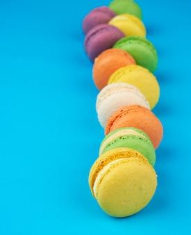 Круглые разноцветные запеченные макаруны со сливками лежат в ряд на синем фоне