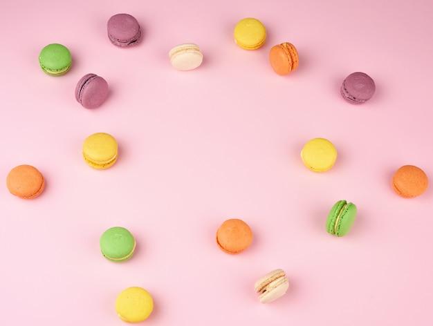 Множество разноцветных круглых печеных макаронных пирожных на светло-розовом фоне