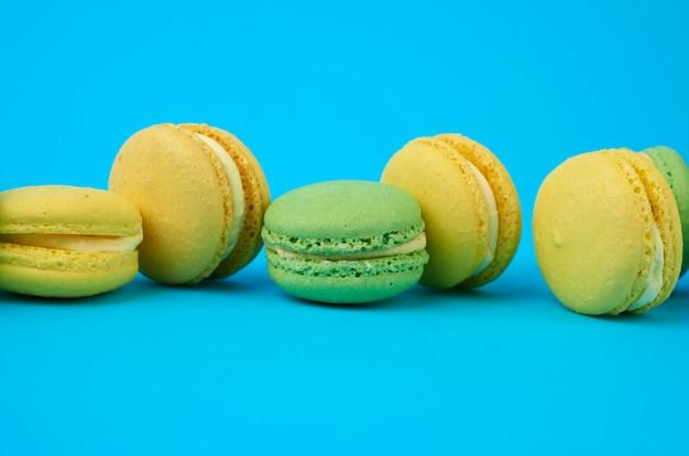Разноцветные круглые печеные пирожные с макаронами на голубом фоне, десерт стоит в ряд