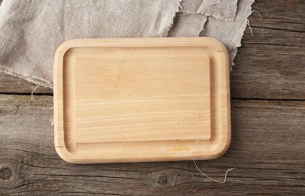 Светло бежевая прямоугольная пустая разделочная кухонная доска на деревянном фоне из старых досок