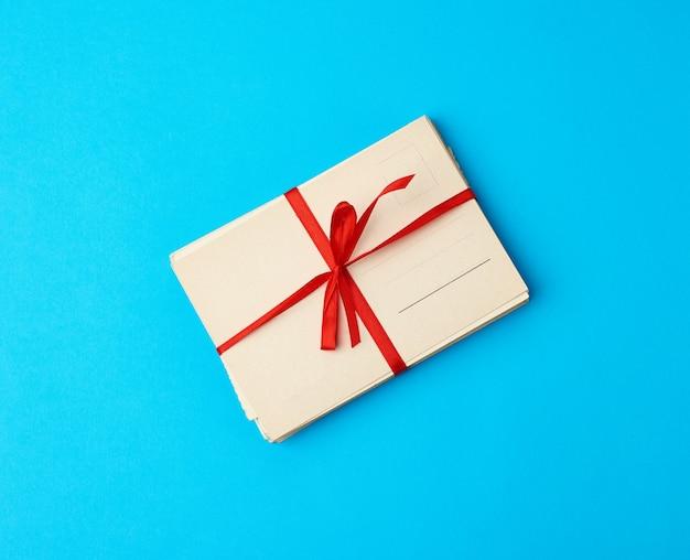赤いシルクリボン長方形のビンテージグリーティングカード、青い背景を縛ら