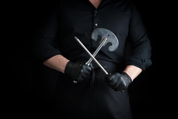 Мужской повар в черной униформе и черных латексных перчатках держит большой острый винтажный нож для мяса и овощей и металлическую точилку