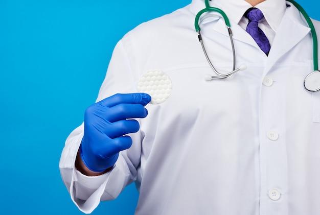 綿の化粧ディスクを保持している白いコート、青いラテックス医療用手袋の男性医師
