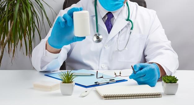 白いコートと青いラテックス手袋の男性医師が彼のオフィスの白い机に座って、錠剤のプラスチック製の白い瓶を保持しています。