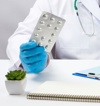 青い滅菌手袋をした男性の手が水疱に薬のスタックを保持しています。