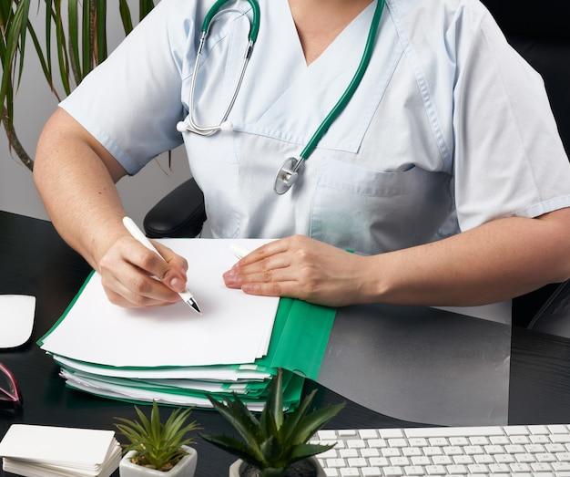 青い制服を着た女性医師がフォームに処方箋を書き、セラピストが黒いテーブルで椅子に座っています。
