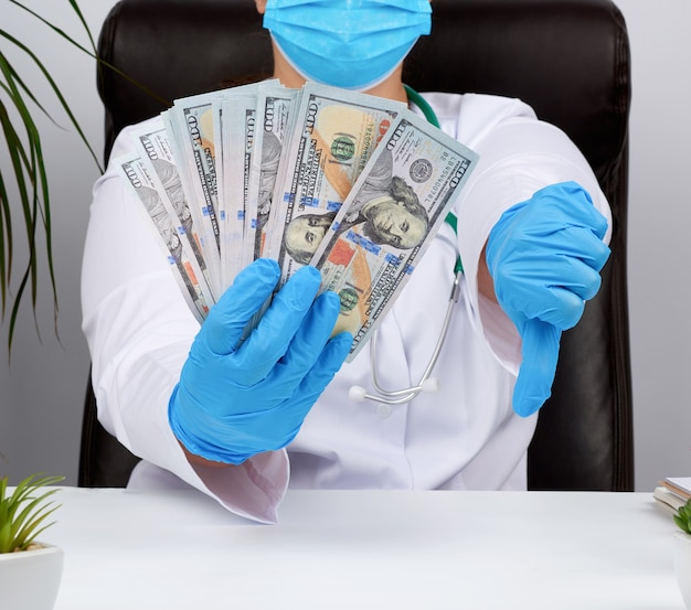 Доктор в белой форме и синих латексных перчатках держит одну руку много денег, а другая показывает плохой жест