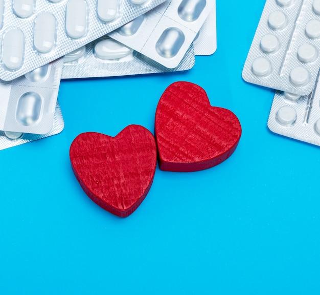 Разные таблетки в упаковке и два красных сердечка