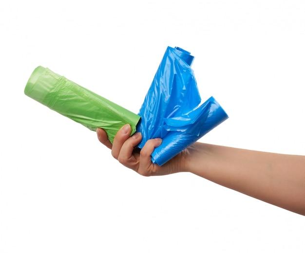 女性の手がゴミの緑と青のビニール袋の束を保持しています。