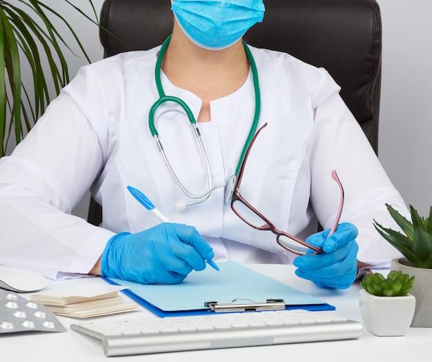 白いコートの若い女性医師、滅菌医療用手袋がフォームに処方箋を書く