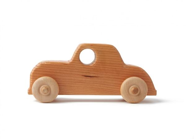 白い表面に分離された車輪を持つヴィンテージの木製子供おもちゃのおもちゃの車