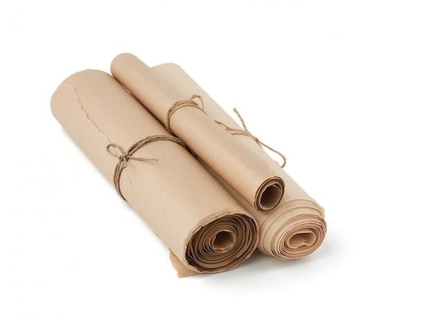 白い背景で隔離された茶色の紙のツイストロールのスタック