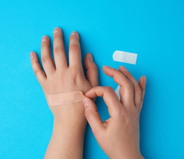 手のひら、補助、青色の背景に接着されたベージュのパッチ