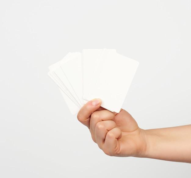 Женская рука держит стопку белых прямоугольных бумажных визиток на белом фоне