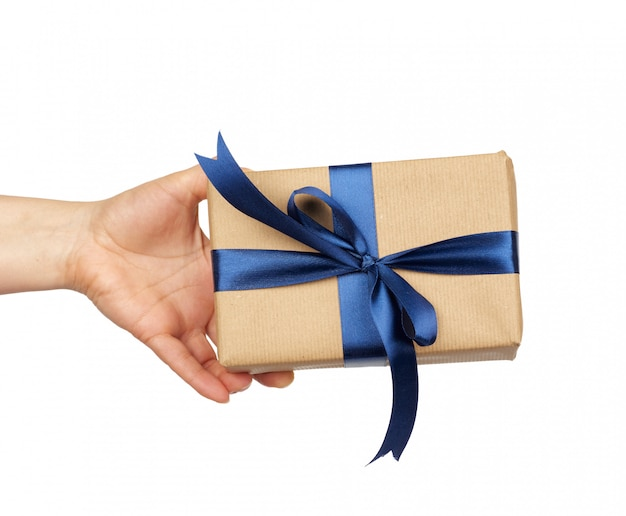 手は結ばれた絹の青い弓と茶色のクラフトペーパーで包まれた贈り物を保持し、件名は白い背景に分離されます