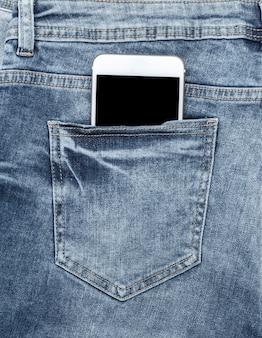Белый смартфон в заднем кармане синих джинсов