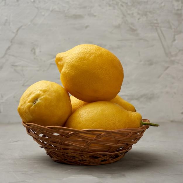 Спелый желтый лимон в плетеной корзине на сером столе
