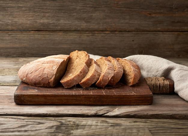 Нарезанный круглый хлеб из ржаной муки на деревянной разделочной доске