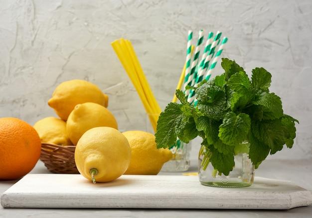Желтый спелый лимон и куча свежей зеленой мяты на деревянной доске