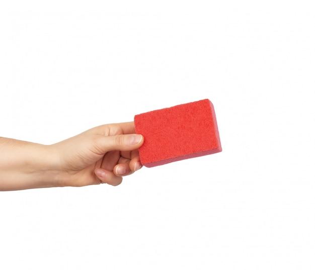 Женская рука держит красную кухонную губку для мытья посуды