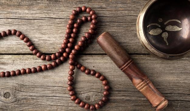 茶色のウーの木製のクラッパーとチベットの歌う銅ボウル