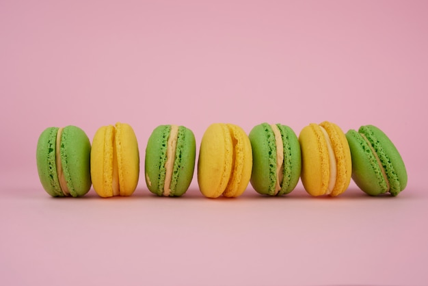 Зеленые и желтые круглые печеные макароны на розовом фоне