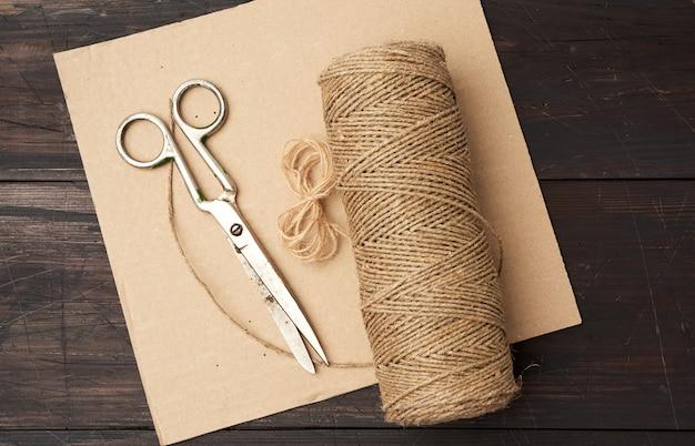 Коричневая нить, скрученная в катушку и старинные металлические ножницы на