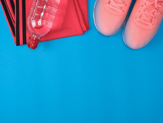 スポーツテキスタイルシューズと青色の背景にフィットネスのための他のアイテム