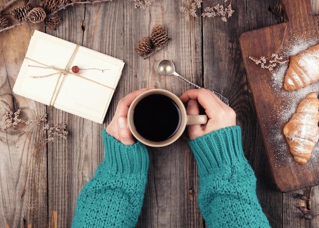 ブラックコーヒーとセラミックのマグカップを保持している緑のニットセーターの女性の手