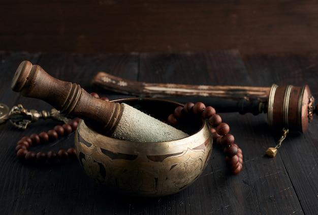 茶色の木製のテーブル、瞑想と代替医療のためのオブジェクトに木製のクラッパーとチベットの歌う銅のボウル