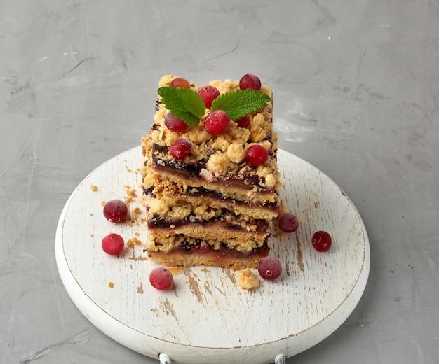 Стек квадратных кусочков запеченного рушиться пирог с голубой сливой на белой деревянной доске, вкусный десерт