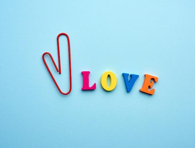 マルチカラーの木製文字とハートの形をした赤いペーパークリップで作られた愛という言葉