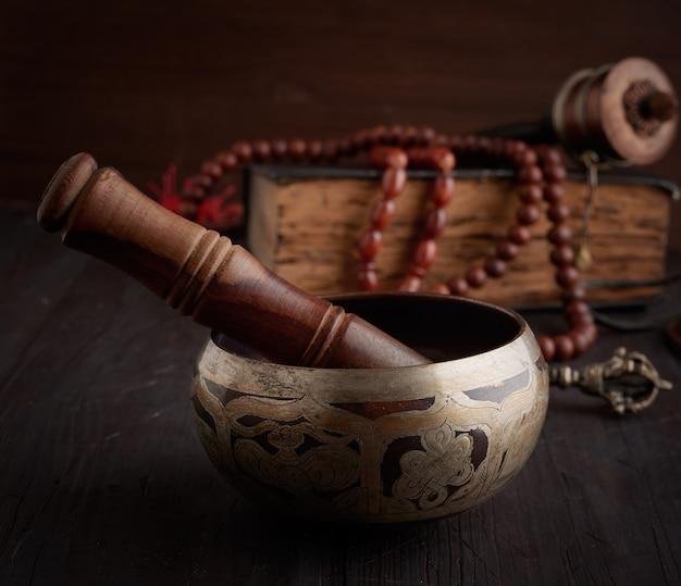茶色の木製のテーブルに木製のクラッパーとチベットの歌銅ボウル