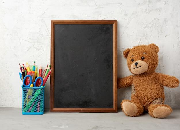 Коричневый плюшевый мишка и пустая деревянная прямоугольная рамка, классная доска для написания списка дел