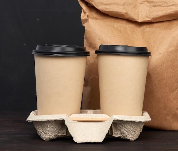 Коричневые бумажные одноразовые стаканчики с пластиковой крышкой стоят в лотке на деревянном столе