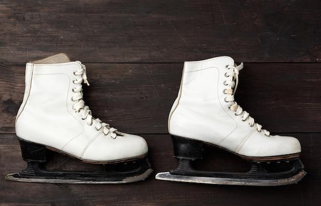 Пара белых кожаных коньков для фигурного катания на коричневой деревянной