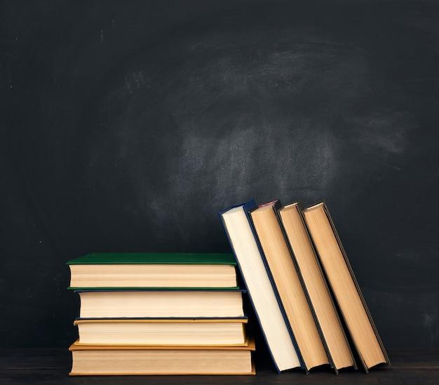 空の黒いチョークボードのスペースにさまざまなハードカバーの本のスタック