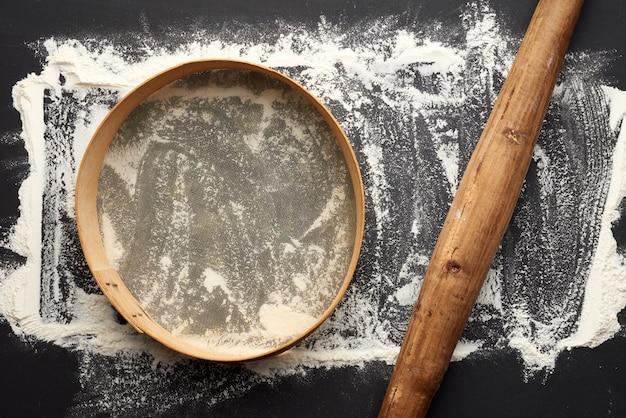 Белая пшеничная мука, разбросанная по черному столу и очень старой коричневой деревянной скалке