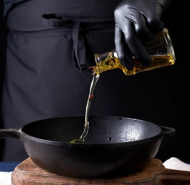 Шеф-повар в черных латексных перчатках наливает оливковое масло из прозрачной бутылки в черную чугунную сковороду