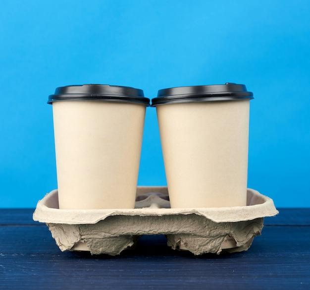 Две коричневые бумажные одноразовые стаканчики с пластиковой крышкой стоят в лотке на деревянном столе
