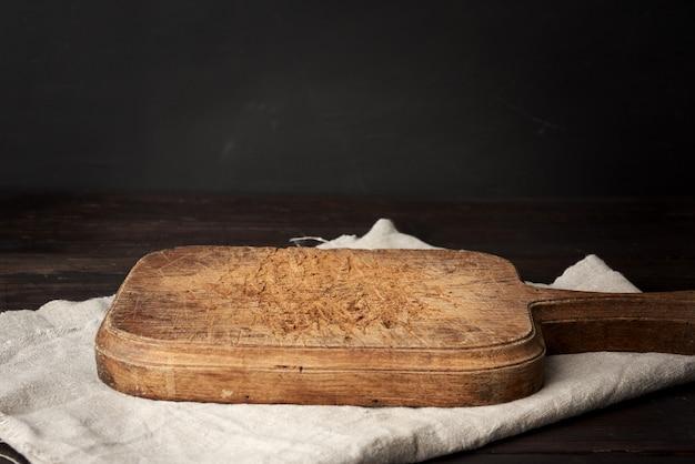 テーブルの上の空のヴィンテージ木製カッティングキッチンボード