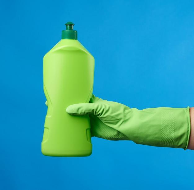 Рука в зеленых резиновых перчатках держит зеленую пластиковую бутылку с моющим средством для мытья посуды